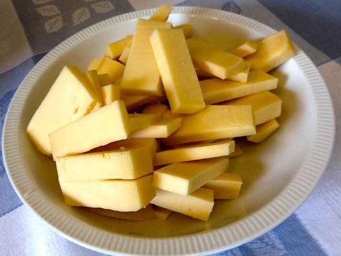 Ein Pfund leckerer Gouda wird gaumenfreundliche Stücke geschnitten.